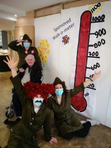 Care team and resident posing with their walk-o-meter to show they have walked 100km.